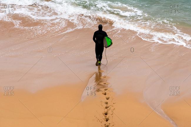 Surfer going into the ocean in Logans Beach, Australia