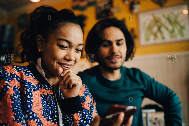 Smiling young man and woman sharing smart phone while sitting at restaurant during brunch