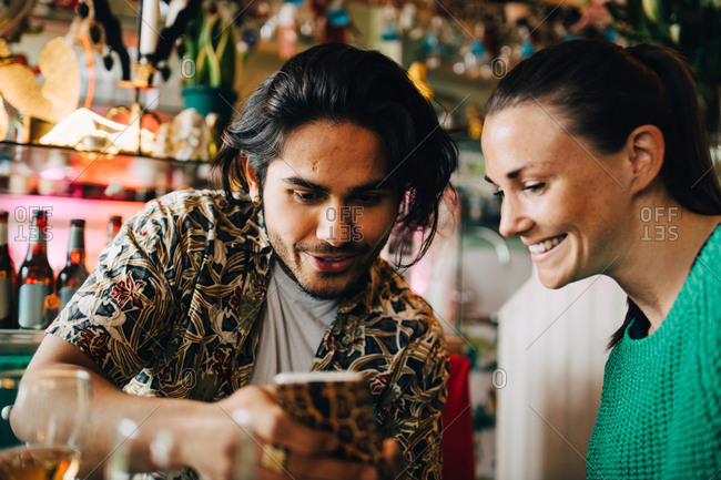 Smiling young man sharing smart phone with woman sitting in restaurant during brunch party