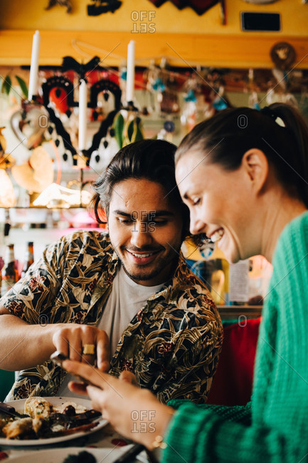 Smiling young man pointing at smart phone to woman sitting in restaurant during brunch party