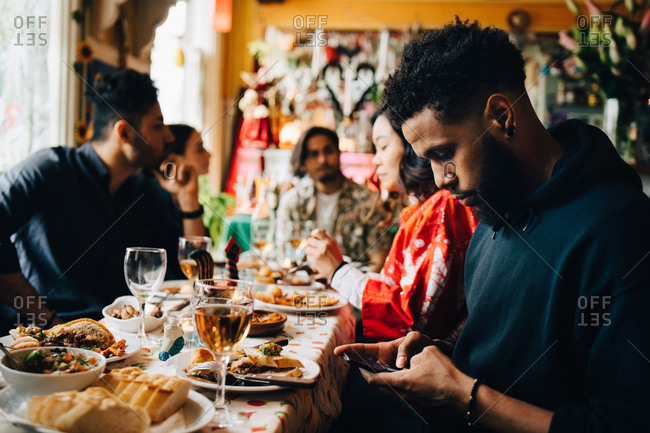 Young man text messaging through smart phone while sitting with friends during brunch party at restaurant