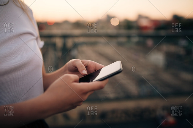 Midsection of young woman using smart phone while standing on bridge in city
