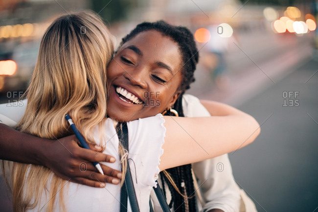 Multi-ethnic female friends embracing each other on street in city