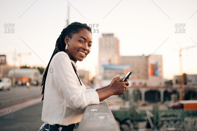 Side view portrait of young woman holding mobile phone while standing on bridge in city