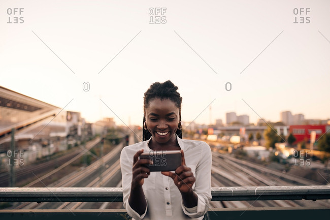 Smiling young woman photographing through mobile phone while standing on bridge against clear sky in city