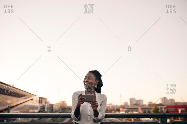 Smiling young woman looking away while holding mobile phone against clear sky in city
