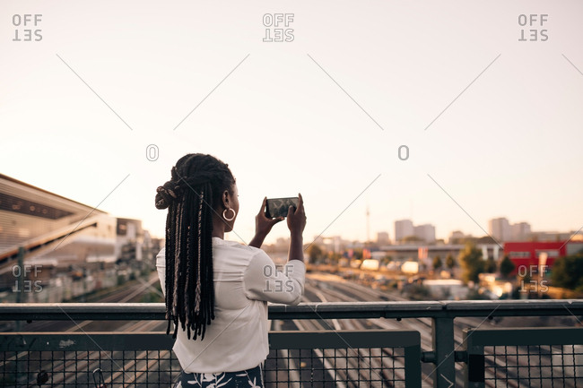 Young woman photographing through mobile phone while standing on bridge against clear sky
