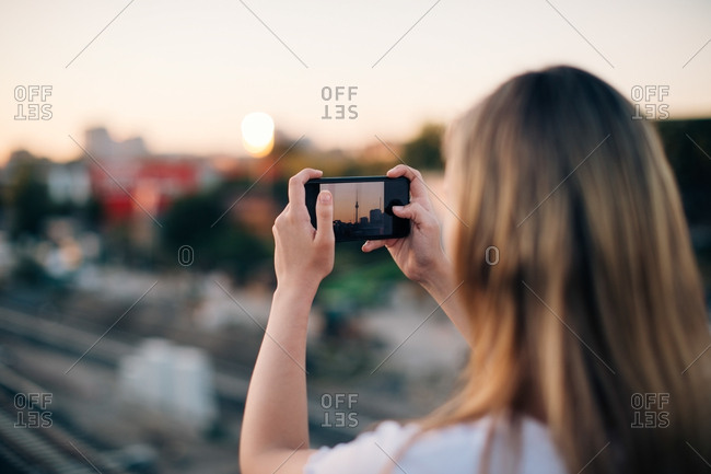 Young woman photographing Fernsehturm through smart phone during sunset