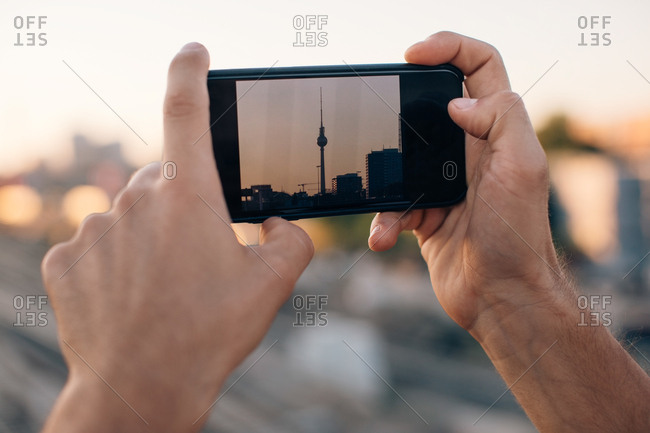 Cropped image of young man photographing Fernsehturm through smart phone during sunset
