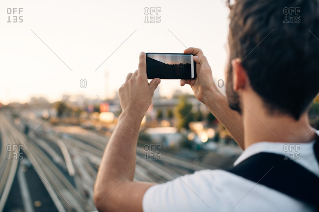 Young man photographing through smart phone over railroad tracks in city