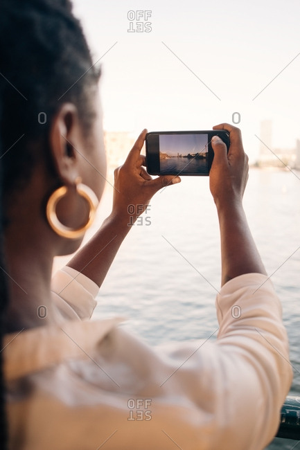Cropped image of young woman photographing river through smart phone in city