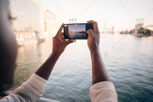 Cropped image of young woman photographing river through mobile phone in city