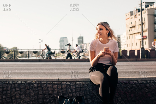 Smiling young woman holding mobile phone while sitting on retaining wall at street