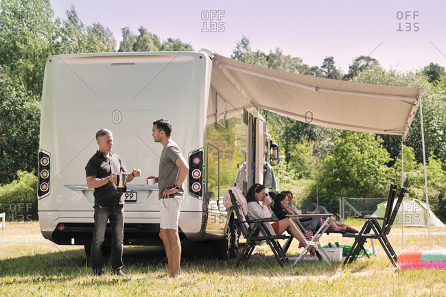 Senior man talking to son while family relaxing outside van at campsite
