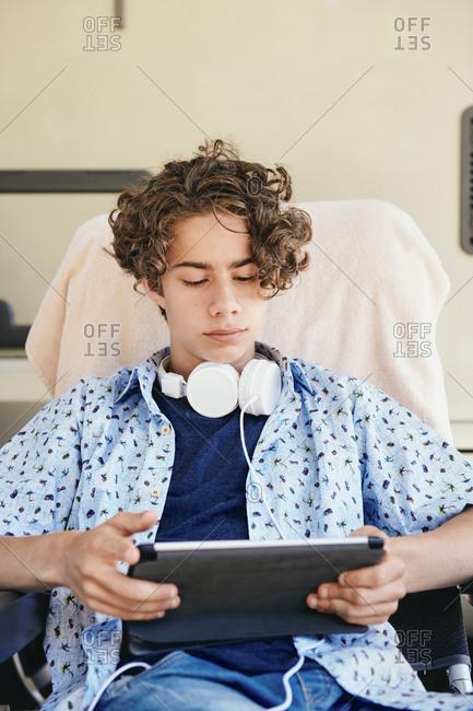 Teenage boy watching movie on digital tablet while sitting against van