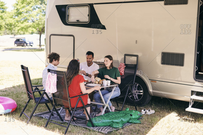Full length of family having food against van while camping at trailer park