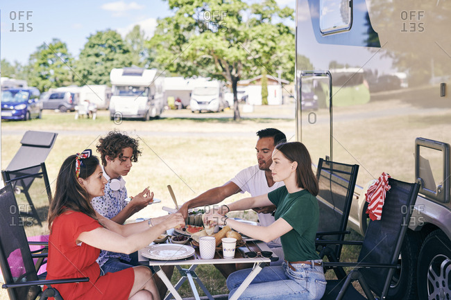 Family enjoying food at table while sitting outside camper van in trailer park