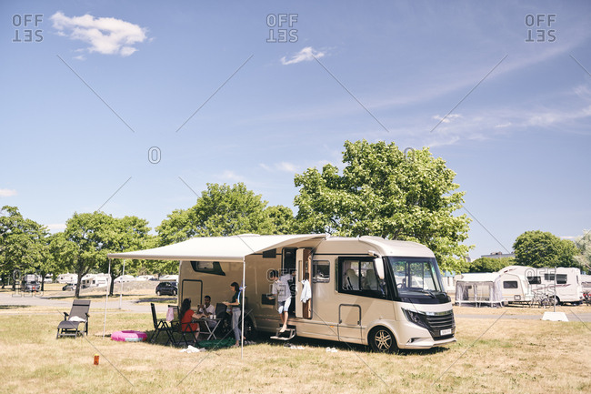 Family camping outside travel trailer at campsite against sky