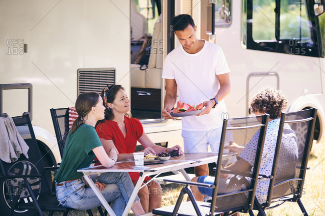 Man serving watermelon slices to family while camping at trailer park
