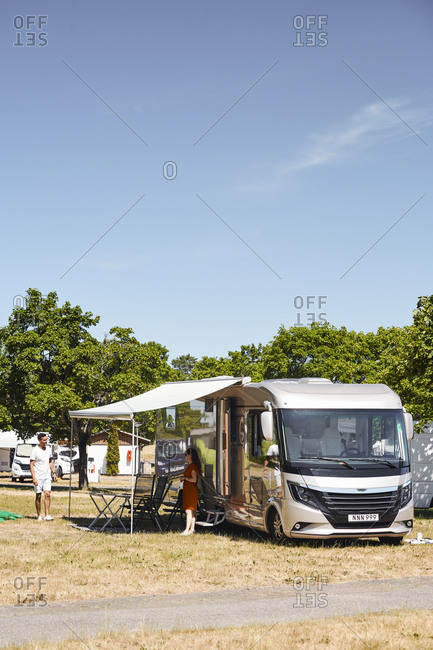 Couple talking while standing outside camper van at trailer park against blue sky