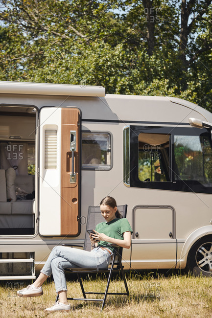 Teenage girl using mobile phone while sitting on folding chair by camper van