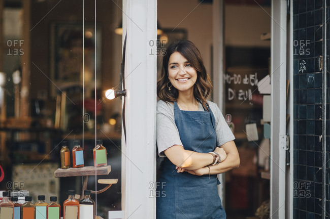Confident female owner looking away while standing at entrance of deli