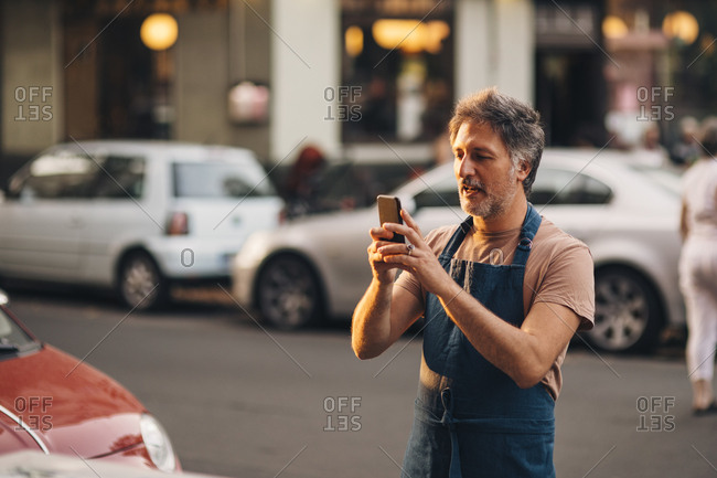 Mature male owner photographing with mobile phone while standing on street