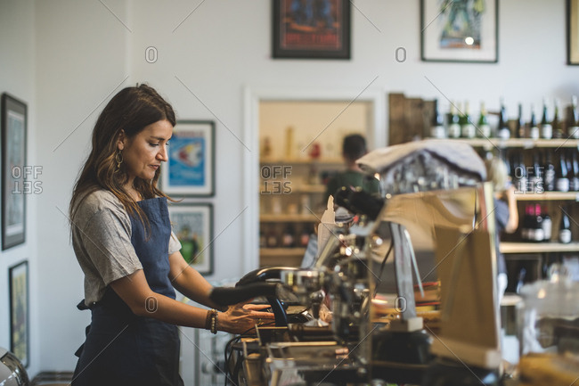 Side view of female sales clerk working at checkout counter in deli
