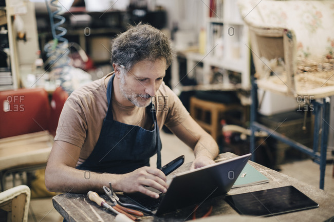 Male upholstery worker using laptop while sitting at workbench in workshop