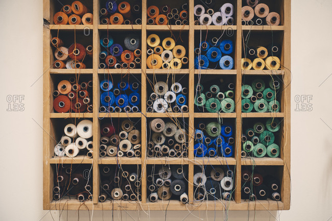 Colorful thread spools in rack at upholstery workshop