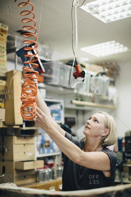 Female upholsterer holding staple gun in workshop