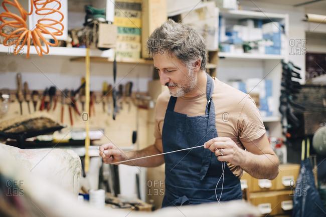 Mature male craftsperson stitching sofa in workshop