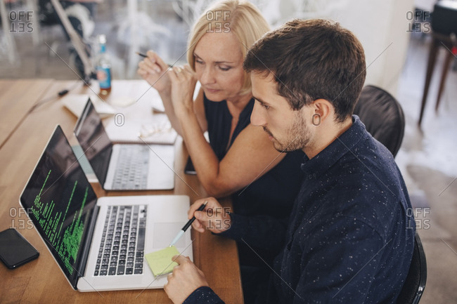 Male computer programmer explaining female colleague over laptop at desk in creative office