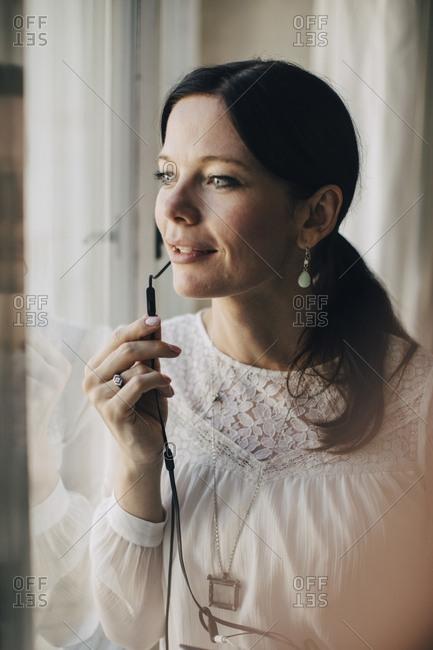 Creative businesswoman talking through earphones by window in office