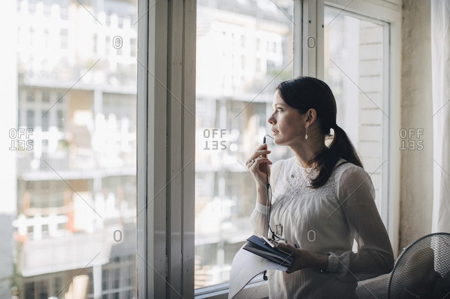 Creative female business professional talking through earphones while standing by window in office