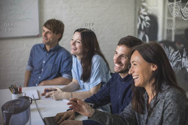 Creative business professionals smiling while sitting at conference table in board room