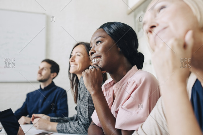 Smiling multi-ethnic business people listening while sitting in board room during meeting