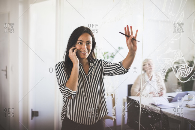 Smiling creative businesswoman gesturing while talking on mobile phone by board room