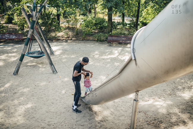Father holding hands of daughter walking on slide at playground