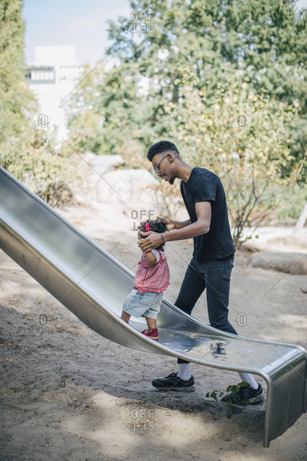 Young man holding hands of daughter walking on slide at playground