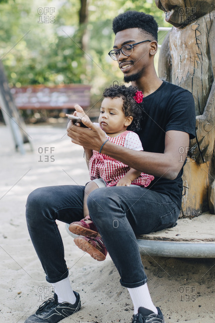 Baby girl using mobile phone while sitting with father on outdoor play equipment at playground