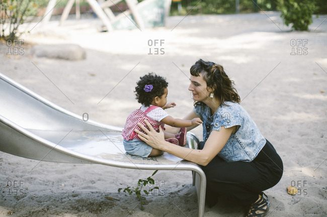 Side view of mother supporting daughter sitting on slide at playground