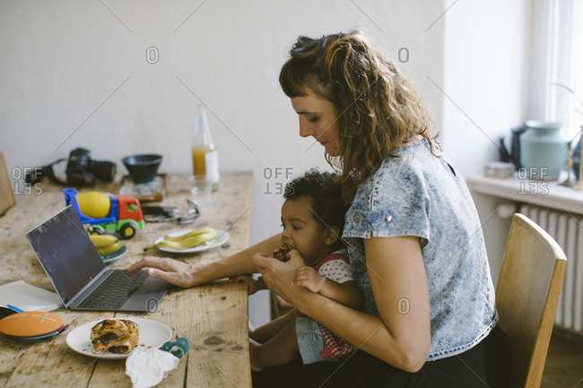 Woman using feeding food to daughter while sitting at dining table in house