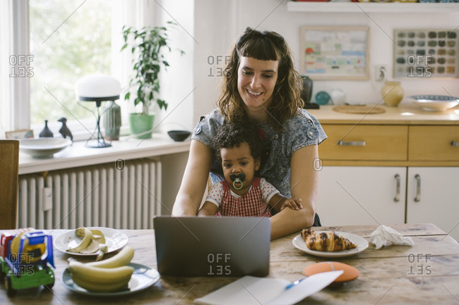 Smiling woman using laptop while sitting with daughter at dining table in house
