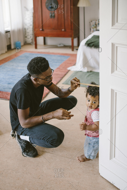 Young man measuring height of daughter at home
