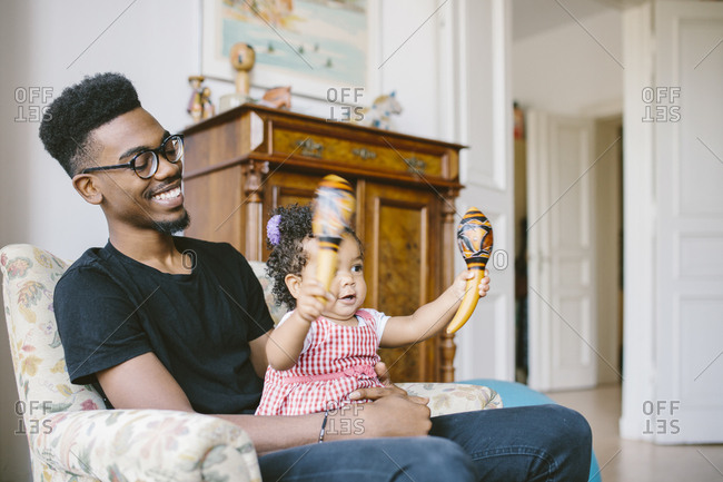 Baby girl holding maracas while sitting with happy father on armchair at home