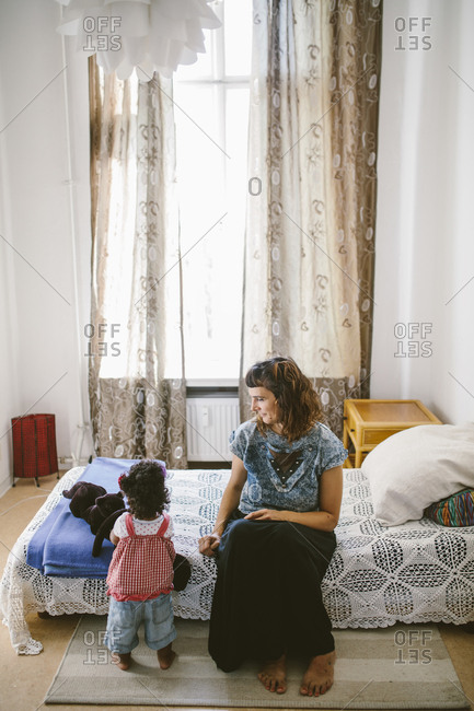 Mother looking at daughter playing with stuffed toy while sitting on bed at home