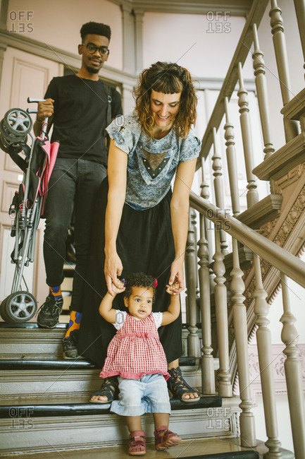Mother holding hands of daughter moving down on steps in apartment