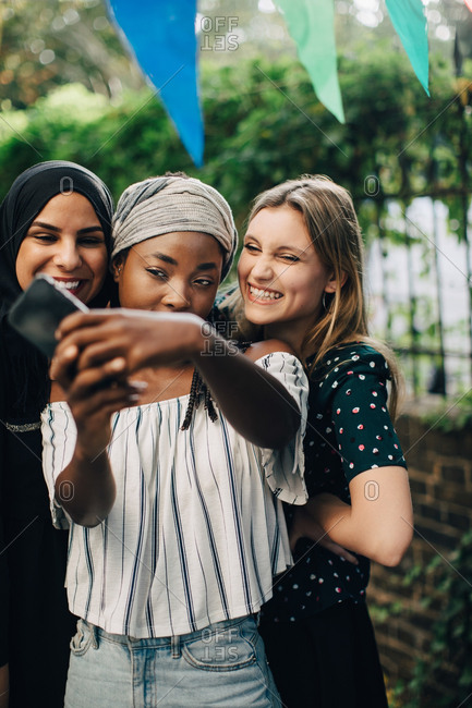 Happy multi-ethnic female friends taking selfie through mobile phone in backyard