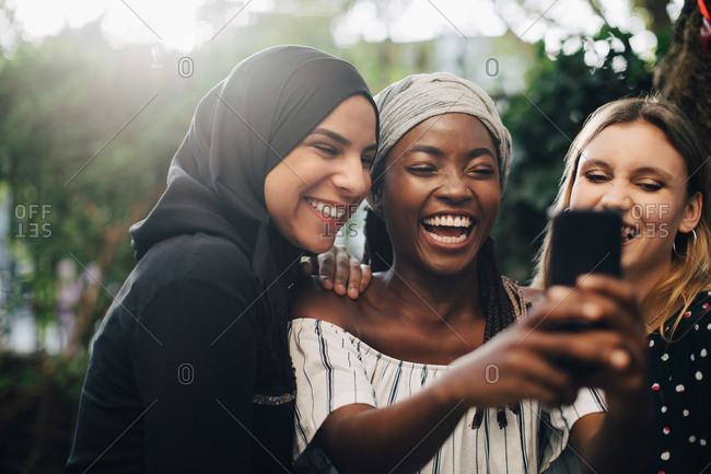 Smiling multi-ethnic female friends taking selfie through mobile phone in backyard